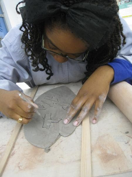 Monet carving into a slab of clay
